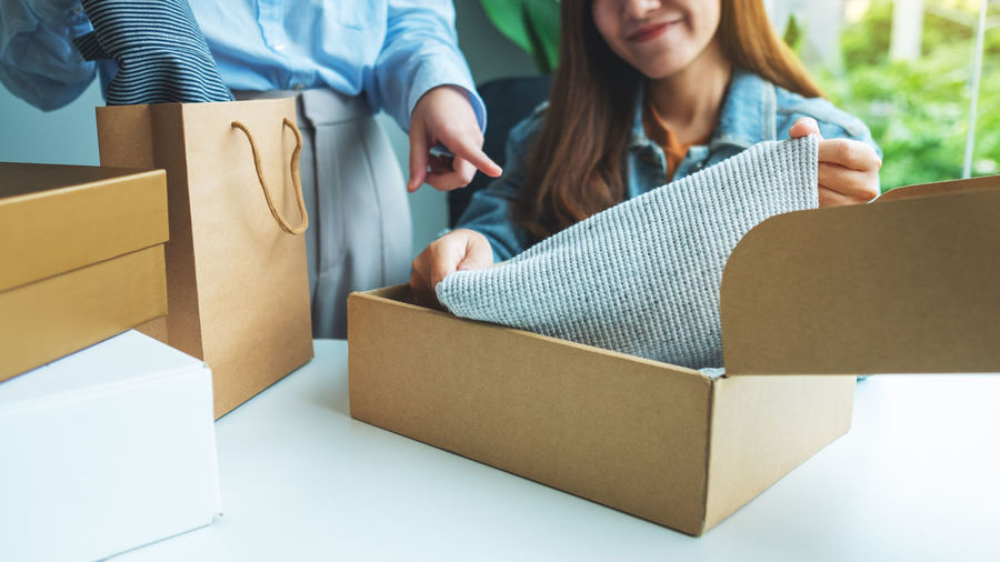 Rear view of people holding paper in box