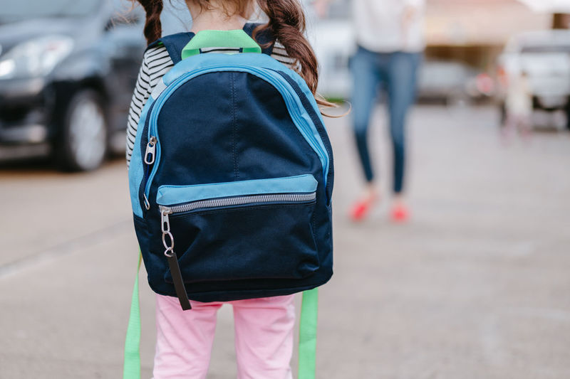 Rear View Of Schoolgirl Waiting For Mother On Footpath