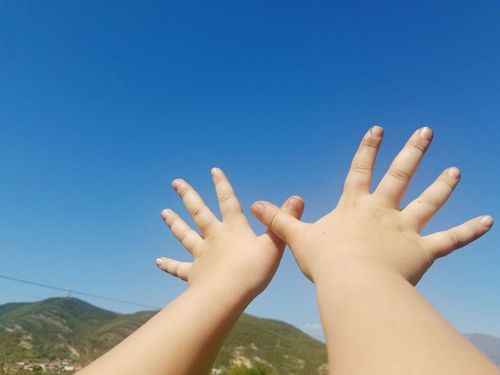 Cropped hands of child gesturing against blue sky during sunny day