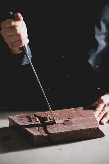 Cropped view of chef cutting chocolate