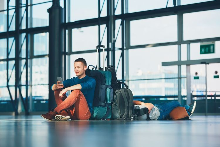 Young man using mobile phone while sitting by luggage at airport