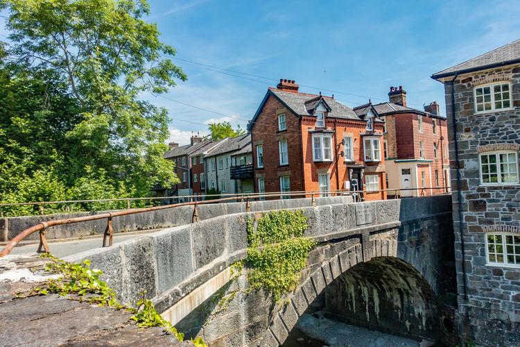 Arch bridge over canal amidst buildings against sky
