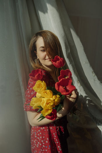 Young woman natural beauty in smells  blooming tulips in light fabric flowing around. spring mood