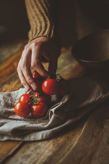 Cropped hand of woman holding cherry tomatoes on table