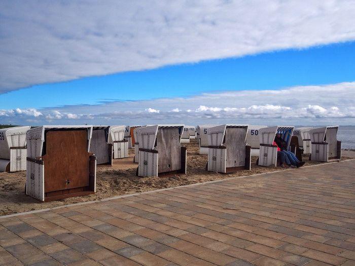 Hooded beach chairs on beach against cloudy sky