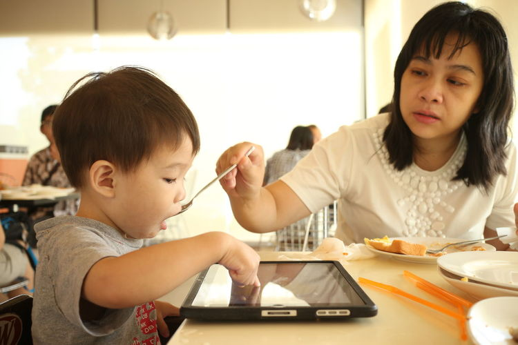 kid with tablet eat breakfast Adult Bonding Breakfast Cheerful Child Childhood Day Domestic Life Domestic Room Eat Family Females Girls Happiness Indoors  Kid Learning Mother People Smiling Togetherness Two People Young Adult