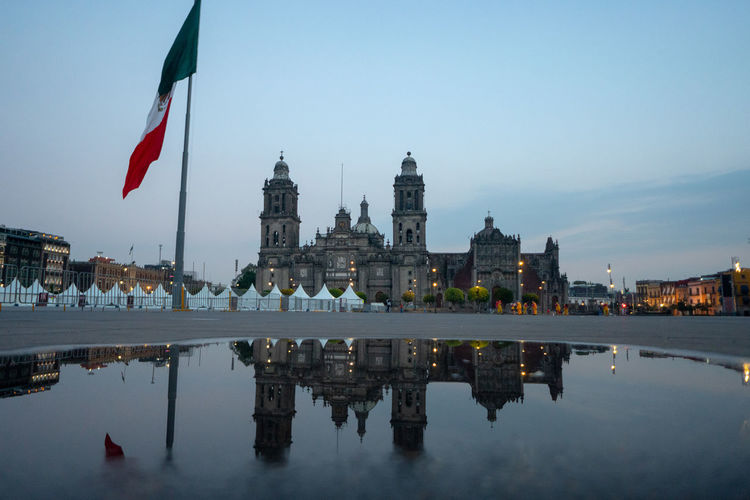 Mexican flag against buildings in city