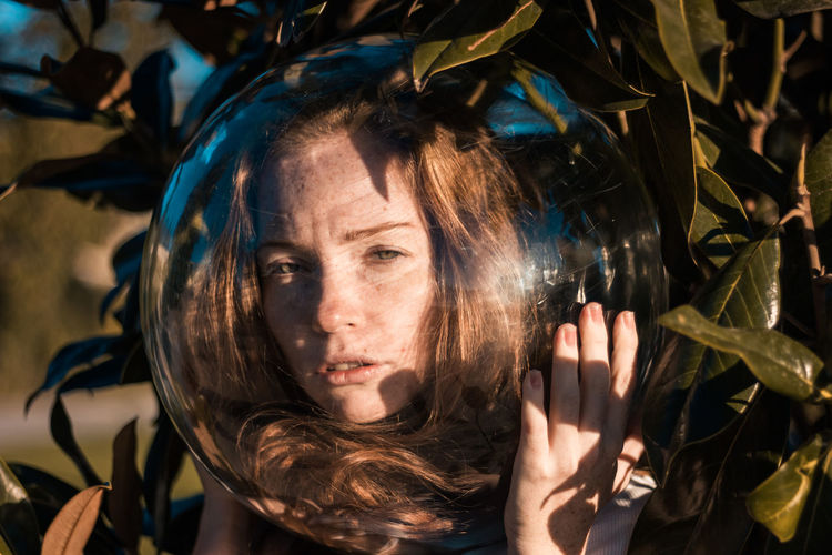 Close-up portrait of young woman wearing glass ball on head against leaves