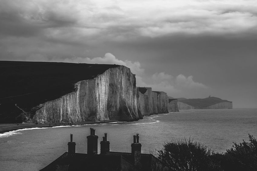 Sky Nature Cloud - Sky Water Day Beauty In Nature Outdoors Tranquil Scene Tranquility Sea No People Scenics Built Structure Architecture Mountain Hydroelectric Power Blackandwhite Beachy Head Black And White Beach Pebble Beauty In Nature Seven Sisters Nature Tranquility The Great Outdoors - 2017 EyeEm Awards