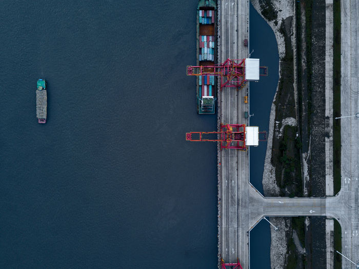 Aerial view of cranes on bridge by cargo ship over sea