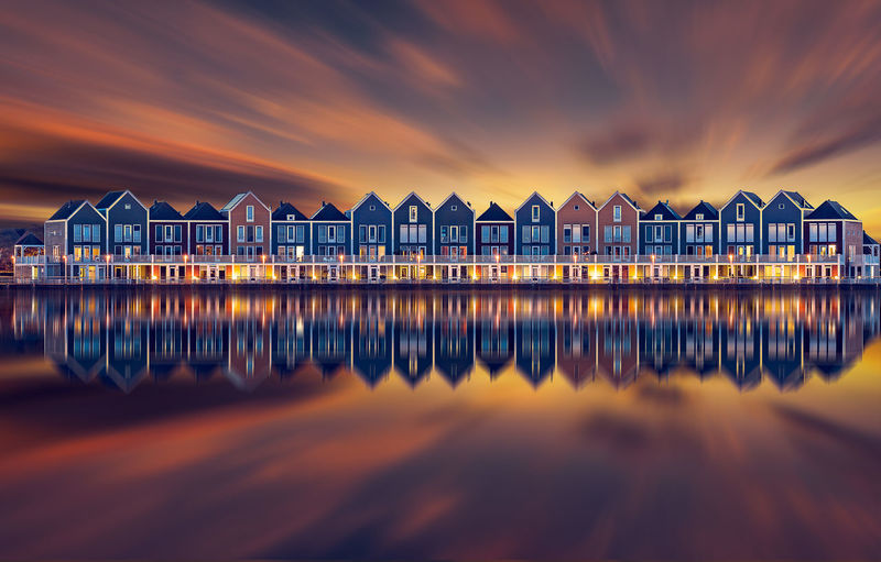 Symmetry view of buildings by sea against sky