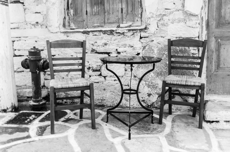 two old chairs with a table outside of a greek kafenion Black And White Friday Chair Day Daylight Greek Kafenion No People Old Old-fashioned Outdoors Table The Traveler - 2018 EyeEm Awards The Still Life Photographer - 2018 EyeEm Awards