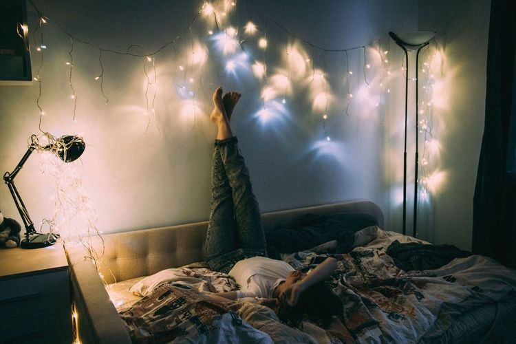 Woman lying on bed in illuminated room