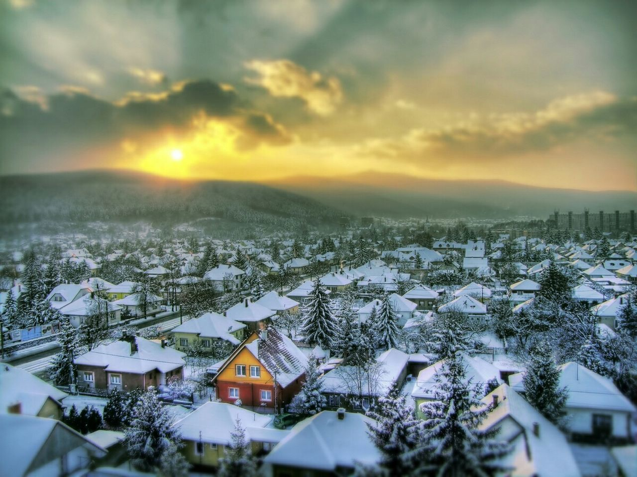 High Angle View Of Snow Covered Residential District Against Sky During Sunset