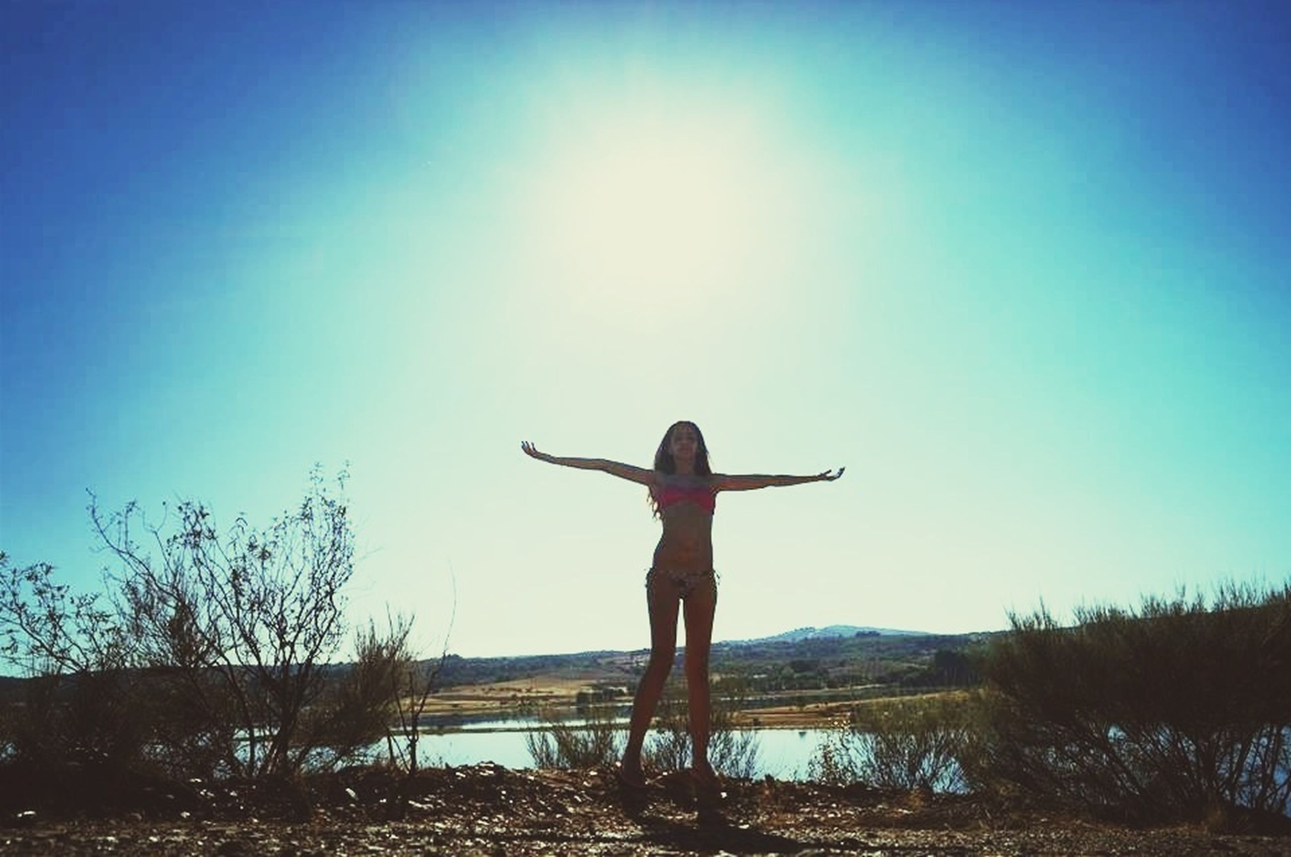 full length, lifestyles, leisure activity, standing, water, clear sky, arms outstretched, blue, casual clothing, sky, tranquility, young adult, tranquil scene, rear view, sunlight, three quarter length, nature, arms raised