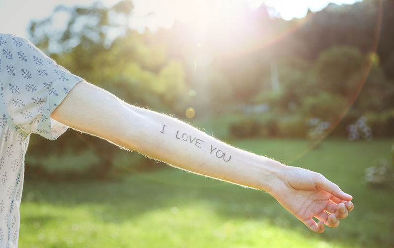 Closeup of male arm with the text -I love you- written in the skin over a sunny nature background Crossed Horizontal Love Nature Sunlight Sunny Text Writing Arm Emotion Handwriting  Human Body Part Ink Letter Message Outdoors Phrase Real People Sentence Skin Summer Sun Tattoo Unrecognizable Person Words