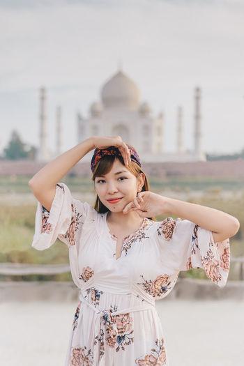 Portrait of woman standing against taj mahal