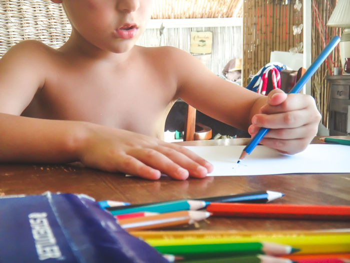 Midsection of shirtless boy drawing on paper at home