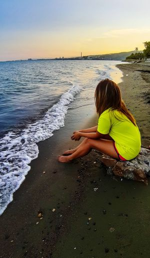 Full length of woman sitting on shore at beach