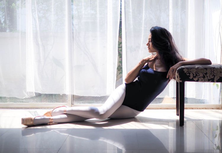 Full length of ballet dancer sitting by chair at home