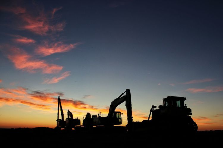 Silhouette construction site against sky during sunset