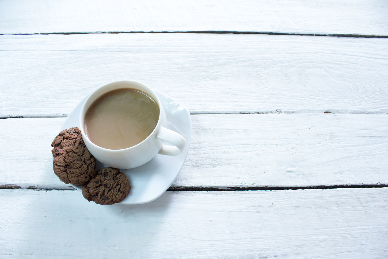 Close-Up Of Coffee Cup With Cookies On Table