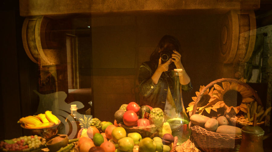 Woman photographing artificial fruits in display cabinet at museum
