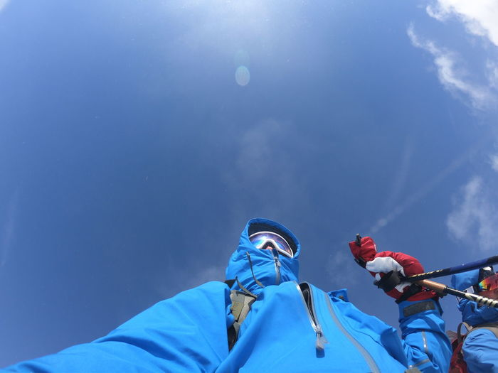 Low angle view of man against blue sky