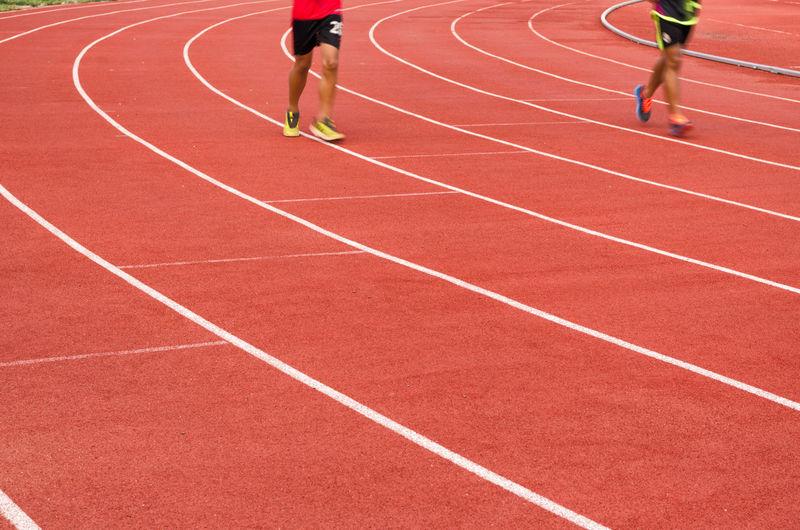 Full length of men running on sports track