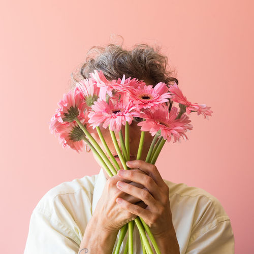 Portrait of mature woman holding pink flowers against colored background