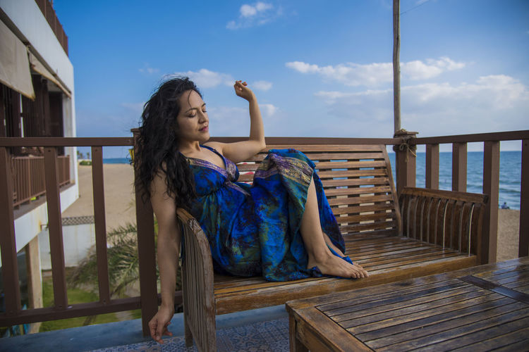 Young woman relaxing on bench in balcony against sea