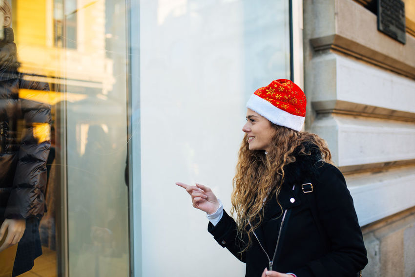 Young attractive woman with santa claus hat in front of shopping window looking to buy something Boutique Business Sale Shopping Standing Window Shopping Buying Consumerism Customer  Gift Leisure Activity Lifestyles One Person Real People Retail  Santas Hat Shopaholic Shopping Bag Shopping Mall Standing Store Store Window Street Warm Clothing Window