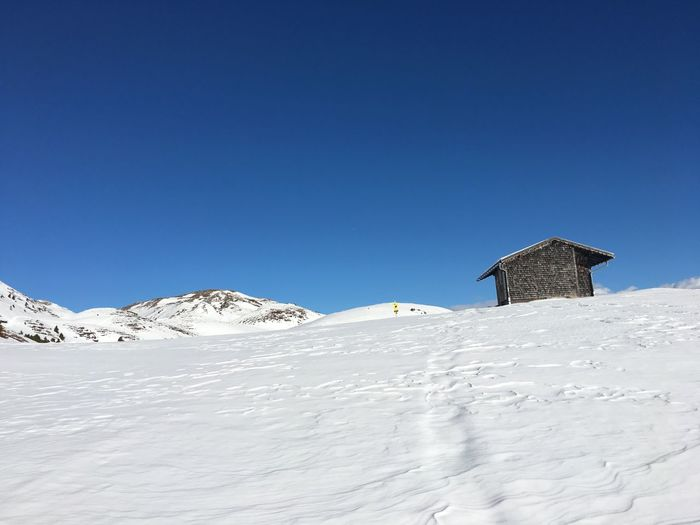Built Structure On Snowcapped Mountain Against Clear Blue Sky