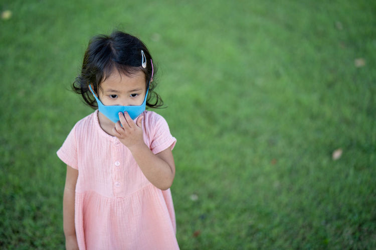 Girl wearing healthy face mask prevent pm2.5 walking outdoor.