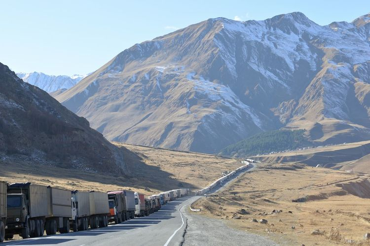 Trucks On Road Leading Towards Mountain During Winter