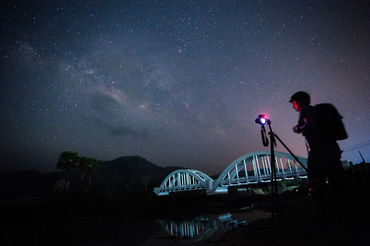 Man photographing on camera against sky at night