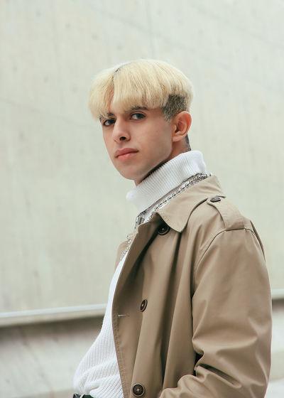 Portrait of teenage boy standing against wall