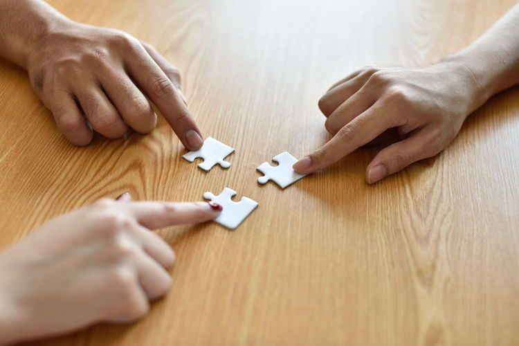 Cropped hands playing jigsaw puzzle at table