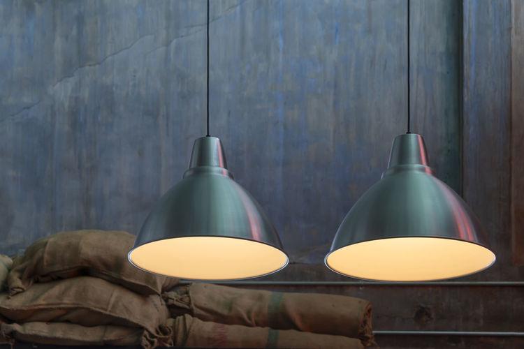 Close-up of illuminated lamp against wall