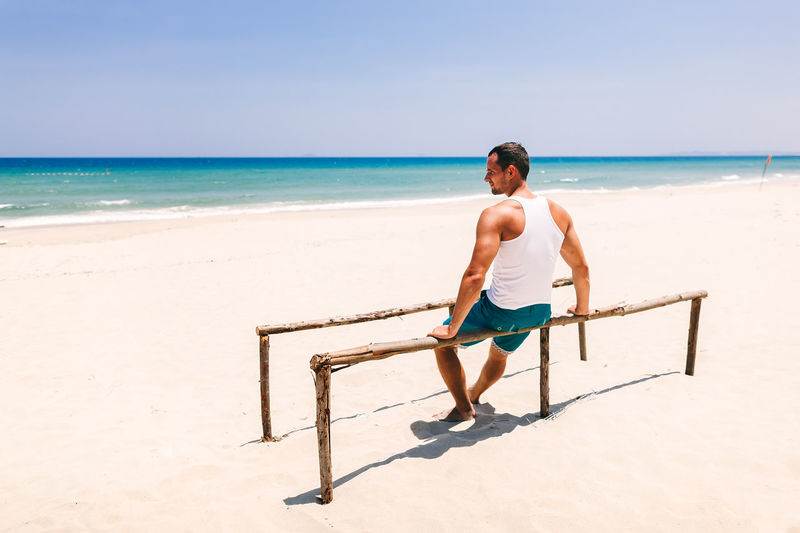 Rear view of man sitting on parallel bars at beach during sunny day