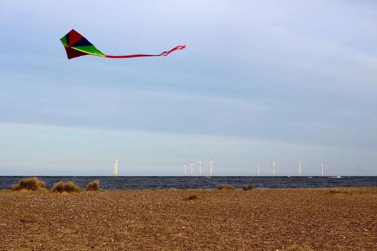 Kite flying over lake against sky