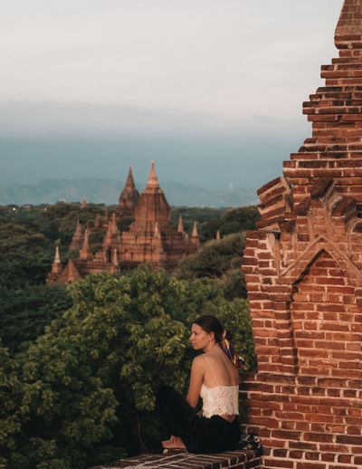 Woman sitting and watching the sunrise over the temples of Bagan, Myanmar Mandalay Nature Sitting Temples Travel Travel Photography Trees View Bagan Bagan, Myanmar Burma Casual Clothing Forest Full Length Landscape Looking At View Myanmar One Person One Woman Only Portrait Sky Sunrise Temple