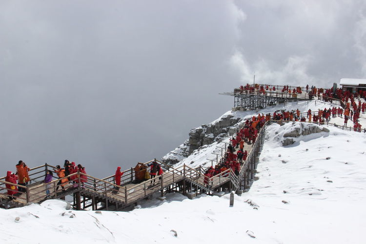 Group of people on snow covered mountain against sky