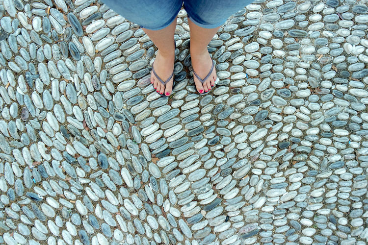Low section of woman standing on cobblestoned footpath