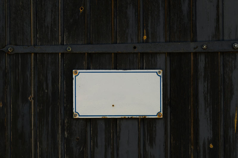 Full frame shot of wooden door with board