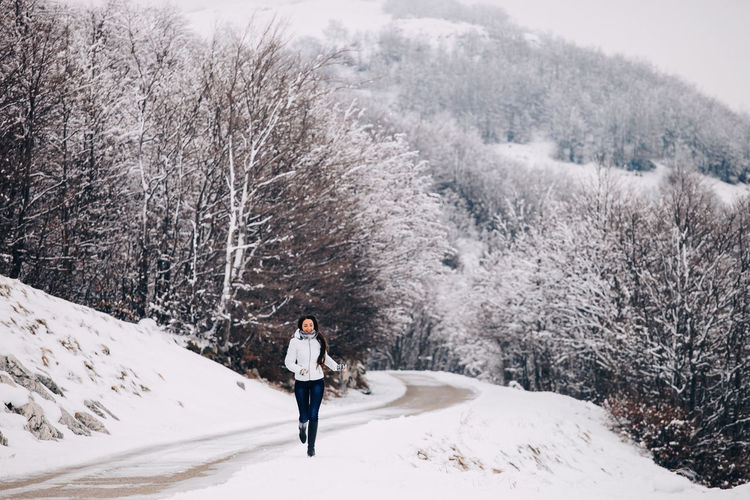Full Length Of Woman Running On Snow Covered Road