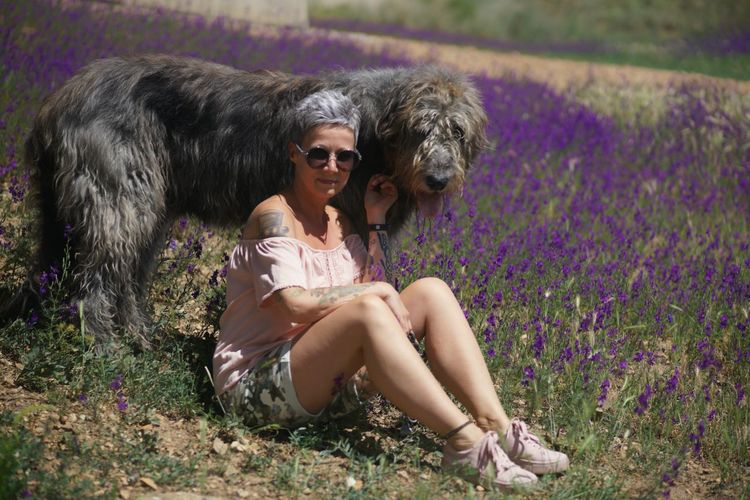 Portrait Of Woman With Dog Sitting On Field