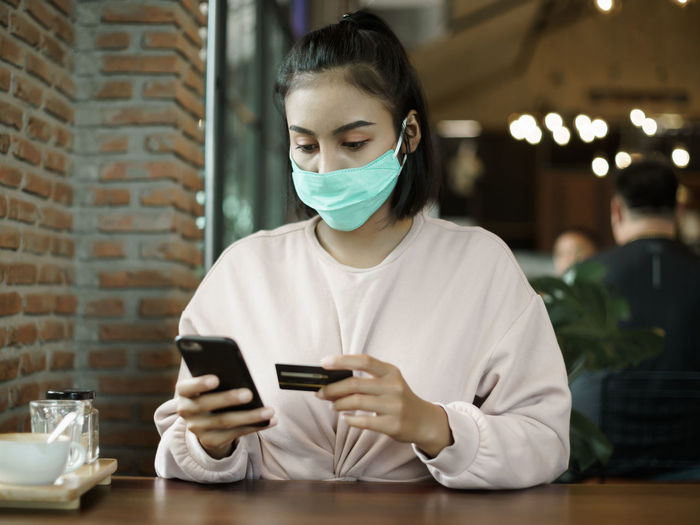 Young woman using smart phone on table at window