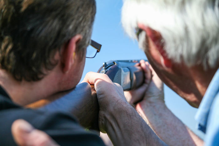 One man teaches another how to aim a rifle at a clay pigeon shooting range Teach Coach Aim Rifle Clay Pigeon Shoot Novice Expert Stag Party Event Looking Down The Barrel Of A Gun Hunt Practice Gun Ready Target Steady Sport Game Outdoor EyeEmNewHere