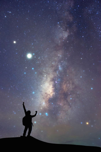 Milky way on night sky and silhouette man on the mountain,  high iso with noise.